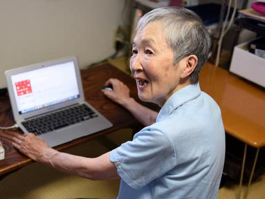 Masako Wakamiya (82) menggunakan laptop di rumahnya daerah Fujisawa, Prefektur Kanagawa, Jepang, 13 Juli 2017. Wakamiya kini menyandang predikat sebagai pengembang atau developer aplikasi berusia paling tua di raksasa gadget Apple. (Kazuhiro NOGI/AFP)