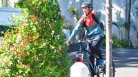 Ahmad Bustomi bersepeda setelah hadir dalam sesi latihan Arema di Lapangan Universitas Muhammadiyah Malang (UMM), Sabtu (8/6/2020). (Bola.com/Iwan Setiawan)