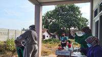 Tenaga medis melakukan tes swab antigen kepada bocah tujuh tahun di Setu, Kabupaten Bekasi, yang baru kembali dari mudik. (Istimewa)