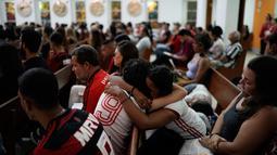Dua wanita mengenakan jersey Flamengo berpelukan saat Misa peringatan untuk para korban kebakaran di akademi sepakbola Brasil, di Rio de Janeiro, Brasil (8/2). Kebakaran merajalela ketika para peman sedang tertidur pulas. (AP Photo/Leo Correa)