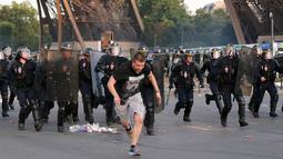 Sejumlah petugas mengejar seorang demonstran yang melarikan diri saat akan diamankan di bawah Menara Eiffel di dekat zona penggemar Paris sebelum laga Portugal vs Prancis di Final EURO 2016 di Prancis (10/6). (REUTERS/Stephane Mahe)