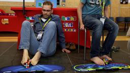 Peserta saat berlatih untuk memecahkan permainan rubik dengan kaki pada Kejuaraan Rubik Eropa  di Praha , Republik Ceko , (15/7).Salah satu kompetisi Rubik terbesar ini diikuti lebih dari 500 peserta. (REUTERS / David W Cerny)