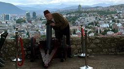 Seorang pria Muslim Bosnia bersiap menyalakan meriam kembang api di kota tua Sarajevo, (16/5). Tembakan meriam kembang api saat matahari terbenam menandai akhir dari puasa selama bulan suci Ramadan. (AFP Photo/Elvis Barukcic)