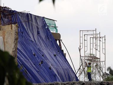 Petugas melihat sisa robohnya bangunan proyek Apartemen Pakubuwono Spring 3 yang ditutupi terpal di Jalan Teuku Cut Nyak Arief, Jakarta, Rabu (27/12). Akibat insiden ini, tiga orang tewas. (Liputan6.com/JohanTallo)