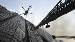 Sebuah helikopter membawa air menyiramkan air ke gedung kantor yang terbakar di Dhaka (28/3). Kebakaran besar melanda gedung perkantoran yang menewaskan sedikitnya lima orang dan lainnya masih terperangkap dalam gedung yang terbakar tersebut. (AFP/Munir Uzzaman)