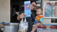 Seorang ibu menunjukkan makanan tambahan yang didapat usai mengikuti pemeriksaan rutin kesehatan bayi di Posyandu Ria Balita, Cipinang, Jakarta, Selasa (16/7/2019). Presiden Joko Widodo fokus pada kesehatan ibu hamil dan anak. (merdeka.com/Iqbal Nugroho)