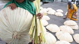 Perajin membawa caping khas Banjar yang selesai dibuat di kawasan Pasar Apung Kuin, Kalimantan Selatan, Senin (26/3). Caping atau tanggui ini biasa digunakan untuk menghindari terik matahari serta hujan. (Liputan6.com/Immanuel Antonius)