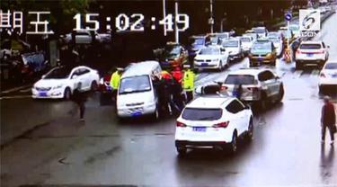 Sekelompok orang berusaha menyelamatkan pengendara motor yang terperangkap di bawah mobil.