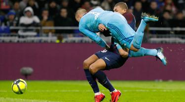 Bomber Paris Saint-Germain, Kylian Mbappe berbenturan dengan kiper Olympique Lyon, Anthony Lopes dalam lanjutan Ligue 1 di Groupama Stadium, Senin (22/1). Lopes tak sengaja menerjang Mbappe hingga terjatuh saat hendak merebut bola. (AP/Laurent Cipriani)