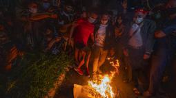 Warga Myanmar yang tinggal di Thailand membakar gambar Jenderal Min Aung Hlaing saat protes di depan Kedutaan Besar Myanmar di Bangkok, Thailand, Kamis (4/2/2021). Jenderal Min Aung Hlaing menjadi tokoh di balik kudeta militer Myanmar pada 1 Februari 2021. (AP Photo/Sakchai Lalit)