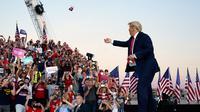 Presiden Donald Trump melemparkan masker dari atas panggung ke kerumunan pendukung saat berkampanye di Bandara Internasional Orlando Sanford di Sanford, Florida, Senin (12/10/2020). Donald Trump kembali berkampanye untuk pertama kalinya usai dinyatakan negatif Covid-19. (AP Photo/Evan Vucci)