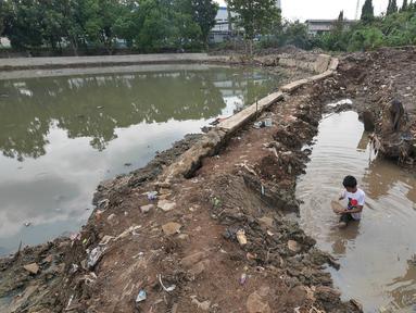 Seorang anak mencari ikan di situ Pedongkelan, Cimanggis, Depok, Rabu (28/11). Proyek normalisasi Situ Pedongkelan mengakibatkan keberadaan tumpukan lumpur bercampur sampah yang mengepung areal permukiman warga. (Liputan6.com/Herman Zakharia)