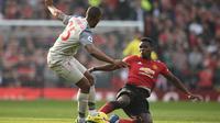 Paul Pogba mencoba menghalau tendangan Daniel Sturridge pada laga lanjutan Premier League yang berlangsung di stadion Old Trafford, Manchester, Minggu (24/2). Man United bermain imbang 0-0 kontra Liverpool. (AFP/Oli Scarff)