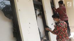 Pekerja membersihkan sisa pecahan kaca di salah satu bagian gedung Bawaslu akibat kericuhan massa aksi di perempatan Jalan MH Thamrin, Jakarta, Kamis (23/5/2019). Sebelumnya, aksi unjuk rasa yang dilakukan massa pada Rabu (23/5) berakhir ricuh. (Liputan6.com/Helmi Fithriansyah)