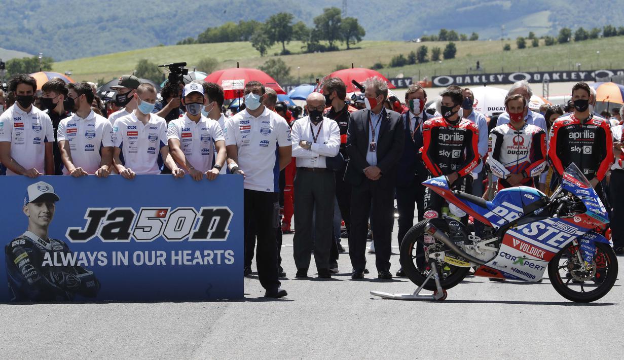 Anggota tim CarXpert PrustelGP beserta sejumlah pebalap MotoGP melakukan penghormatan terakhir bagi Jason Dupasquier sebelum dimulainya balapan MotoGP Italia di Sirkuit Mugello. (Foto: AP Photo/Antonio Calanni)