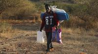 Pengungsi Ethiopia berjalan di wilayah Qadarif, Sudan, Rabu (18/11/2020). Badan Pengungsi PBB mengatakan konflik yang berkembang di Ethiopia telah mengakibatkan ribuan orang melarikan diri dari wilayah Tigray ke Sudan. (AP Photo/Marwan Ali)