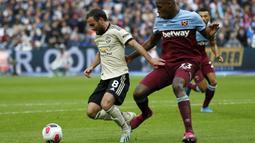 Gelandang Manchester United, Juan Mata, berusaha melewati bek West Ham, Issa Diop, pada laga Premier League di Stadion London, London, Minggu (22/9). West Ham menang 2-0 atas MU. (AFP/Ian Kington)