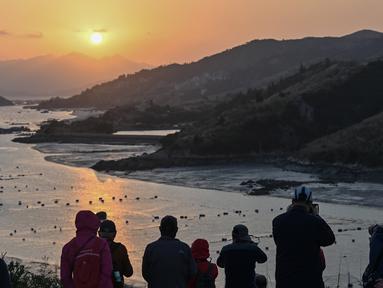 Wisatawan mengambil foto matahari terbenam dari Pulau Dong An di Xiapu, Provinsi Fujian, China, Kamis (12/12/2019). Xiapu menjadi daya tarik tersendiri bagi fotografer pemula karena jauh dari gedung pencakar langit dan hiruk pikuk kota-kota besar di China. (RETAMAL HECTOR/AFP)