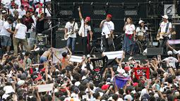 Grup band SLANK saat duet bersama penyanyi Oppie Andaresta tampil membawakan lagu dalam pagelaran Konser Putih Bersatu di Stadion GBK, Senayan, Jakarta, Sabtu (13/4). SLANK menciptakan lagu khusus Capres 01 Jokowi dengan judul #barengjokowi. (Fimela.com/Bambang Eros)