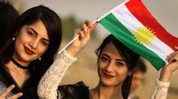Seorang gadis Kurdi Iran memegang bendera Kurdi saat mengampanyekan referendum untuk kemerdekaan di kota Bahirka, Irak Utara (21/9). Mereka meminta referendum untuk menentukan kemerdekaan etnis Kurdi di Irak. (AFP Photo/Safin Hamed)