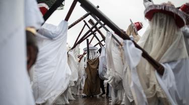 Eyo masqueraders melakukan sebuah gerakan untuk menghibur penonton saat Festival Eyo di Tafawa Balewa Square di Lagos, Nigeria (20/5). (AFP Photo/Stefan Heunis)