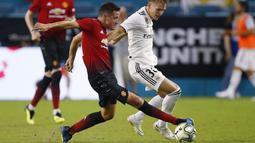 Gelandang Manchester United, Ander Herrera, berebut bola dengan striker Real Madrid, Martin Odegaard, pada laga ICC 2018 di Miami Gardens, Rabu (1/8/2018). Manchester United menang 2-1 atas Real Madrid. (AP/Brynn Anderson)