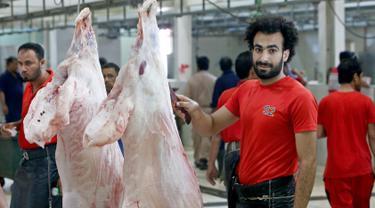 Mohammad Ibraheem saat memotong daging di sebuah rumah jagal hewan di hari ketiga Idul Adha di Kota Kuwait (13/8/2019). Pria 27 tahun ini mendadak terkenal karena kemiripan wajahnya dengan pemain Liverpool asal Mesir, Mohamed Salah. (AFP Photo/Yasser Al-Zayyat)