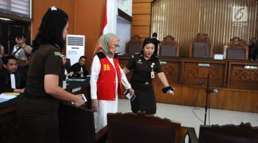 Terdakwa Ratna Sarumpaet dikawal petugas tiba di Pengadilan Negeri (PN) Jakarta Selatan, Kamis (29/2). Ratna menjalani sidang dakwaan perdana atas kasus penyebaran berita hoaks yang menyebutkan wajah lebam. (Liputan6.com/Herman Zakharia)