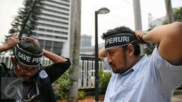 """Massa Serikat Pekerja Peruri memasang ikat kepala bertuliskan """"Save Peruri"""" saat berunjuk rasa di depan Kementerian BUMN, Jakarta, Selasa (19/1). Dalam aksinya, mereka menuntut direksi Perum Peruri untuk mundur . (Liputan6.com/Faizal Fanani)"""