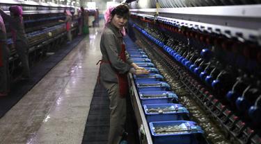 Seorang wanita memilah kepompong ulat sutra saat bekerja di pabrik sutra Kim Jong Suk di Pyongyang, Korea Utara (26/11/2019). Pabrik sutra itu, dinamai menurut nama nenek pemimpin Korea Utara Kim Jong Un. (AP Photo/Dita Alangkara)