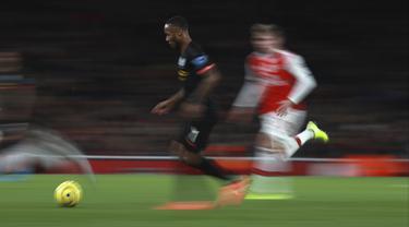 Penyerang Manchester City, Raheem Sterling menggiring bola saat bertanding melawan Arsenal pada lanjutan Liga Inggris di di Stadion Emirates, London (15/12/2019). City menang telak atas Arsenal 3-0. (AP Photo/Ian Walton)