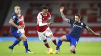 Pemain Arsenal, Joe Willock, berusaha melewati pemain Southampton, Danny Ings, pada laga Liga Inggris di Stadion Emirates, Kamis (17/12/2020). Kedua tim bermain imbang 1-1. (Peter Cziborra/Pool via AP)