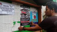 Warga Kampung Sukoharjo Malang memasang poster anti politik uang di pemilu 2019 (Liputan6.com/Zainul Arifin)