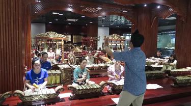 Randy Geovani Putra, seorang guru asal Indonesia, mengajarkan para siswa di China cara memainkan alat musik gamelan. (Xinhua)