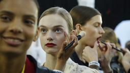 Model saat dirias di belakang panggung sebelum memamerkan koleksi busana wanita Fall Winter 2020 Jil Sander selama Fashion Week di Milan, Italia, Rabu, (19/2/2020). (AP Photo/Domenico Stinellis)