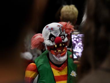 Pengunjung mengambil gambar karakter badut menyeramkan saat acara ScareLA 'Monsters Come Together' di Los Angeles, California (6/8). Acara ini menjadi ajang pertemuan bagi para penggemar film horor. (AFP Photo/Mark Ralston)