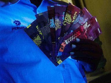 Petugas menunjukan uang kertas rupiah yang disinari lampu ultraviolet saat peruri media visit di Perusahaan Umum Percetakan Uang Indonesia (Peruri), Karawang, Jawa Barat, Rabu (18/1). (Liputan6.com/Faizal Fanani)