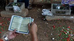 Umumnya para peziarah membawa buku Surat Yasin saat melakuan ziarah kubur, Karet Bivak, Jakarta, Sabtu (18/7/2015). Ziarah kubur dilakukan umat muslim untuk mendoakan mendiang keluarga dan kerabat mereka yang telah meninggal. (Liputan6.com/JohanTallo)