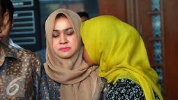 Anak Gatot Pudjo Nugroho memeluk sang ibu Evy Susanti usai menjalani sidang di Pengadilan Tipikor, Jakarta, Rabu (17/2). Jaksa menuntut Gatot dan Evy dengan denda sebesar Rp200 juta subsider lima bulan kurungan. (Liputan6.com/Faisal R Syam)