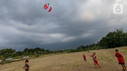 Anak-anak bermain layangan koang di lahan kosong Kampung Sawah, Ciputat, Tangerang Selatan, Selasa (2/6/2020). Layangan koang yang terbuat dari bambu dan mengeluarkan bunyi menyita masyarakat sekitar sebagai hiburan selama pandemi Covid-19. (Liputan6.com/Fery Pradolo)
