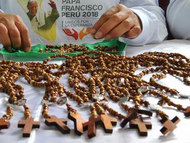 Seorang narapidana di penjara Wanita Virgen de Fatima membuat rosario kayu buatan tangan di Lima, Peru (12/1). Penjara tersebut menghasilkan 33.000 rosario untuk dijual di toko-toko ibukota Peru, Lima. (AFP Photo/Cris Bouroncle)
