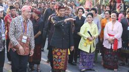 Presiden Joko Widodo dan Ibu Negara Iriana mengenakan pakaian adat Bali tiba menghadiri Karnaval Budaya Bali, Jumat (12/10). Karnaval tersebut untuk mengenalkan kepada delegasi  IMF - WB Group 2018 tentang budaya Bali. (Liputan6.com/Angga Yuniar)
