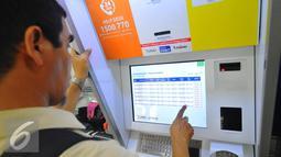Calon penumpang memilih kereta di mesin penjual tiket kereta api otomatis di Stasiun Senen, Jakarta, Selasa (20/12). Jelang libur Natal dan tahun baru tiket Kereta Api sudah habis untuk keberangkatan Jateng dan Jatim. (Liputan6.com/Angga Yuniar)