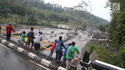 Warga berdiri di jembatan menyaksikan aliran lahar dingin yang melintasi Sungai Yeh Sah di Karangasem, Bali, Sabtu (2/12). Banjir lahar dingin ini juga mengundang pengendara yang melintas untuk berfoto dan melihat-lihat. (Liputan6.com/Immanuel Antonius)