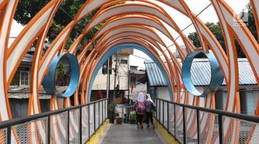 Dua pelajar melintasi Jembatan Ketupat di Jalan Gajah Mada, Petojo, Jakarta, Kamis (8/8/2019). Jembatan Ketupat memiliki bentang 12,5 meter dan lebar 2,5 meter dengan waktu pengerjaan selama 45 hari. (Liputan6.com/Helmi Fithriansyah)