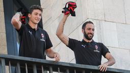Pemain baru AC Milan, Gonzalo Higuain dan Mattia Caldara melempar jersey ke suporter dari balkon di alun-alun pusat Milan Piazza Duomo (3/8). Caldara didapatkan secara permanen dan menandatangani kontrak sampai 30 Juni 2023. (AFP Photo/Stringer)