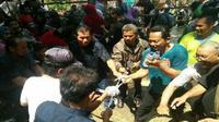 Para pengunjung ritual Larap Selambu Gunung Kemukus saat berebut kain kelambu bekas dan air sisa jamasan. (Foto: Wardoyo)