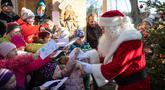 Seorang pria berpakaian Santa Claus disambut anak-anak selama pembukaan kantor surat Natal yang paling terkenal di Himmelpfort, Kamis (14/11/2019). Seperti tahun-tahun sebelumnya pada Natal kali ini Santa Klaus di Jerman sangat sibuk. (Soeren Stache/dpa via AP)