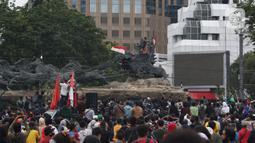 Massa aksi demo tolak omnibus law UU Cipta Kerja naik ke atas patung arjuna wiwaha mengibarkan bendera merah putih di Jalan Medan Merdeka Barat, Jakarta Pusat, Selasa (20/10/2020). Aksi mereka lantas disambut meriah oleh para massa yang masih bertahan. (Liputan6.com/Herman Zakharia)