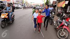 Guru membimbing siswa PSBN Cahaya Bathin penyandang tunanetra mengikuti praktik orientasi mobilitas di Cawang, Jakarta, Selasa (11/4). Praktik itu untuk melatih kemandirian siswa menghadapi situasi apapun dalam kesehariannya. (Liputan6.com/Gempur M Surya)